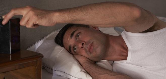 Sleepless man looking at alarm clock