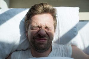 Sleeping man disturbed by sun