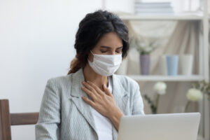 woman wearing mask while sitting at computer