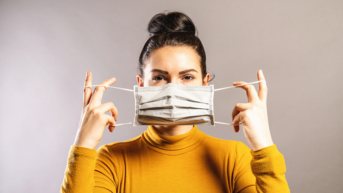 woman putting mask on her face
