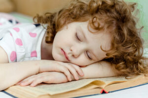 Child sleeping on a book