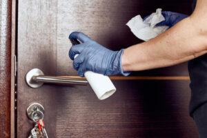 person disinfecting door handle