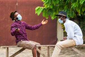 two men sitting on bench wearing masks