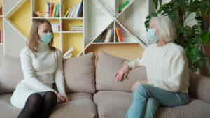 two woman sitting on couch talking and wearing masks