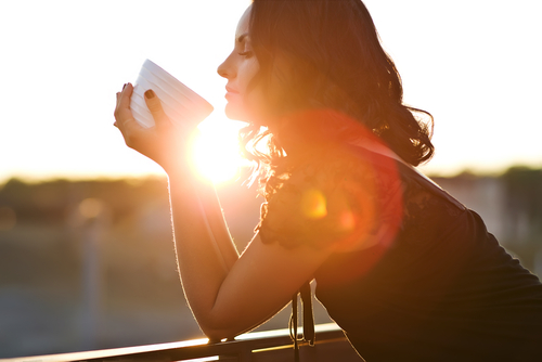 A woman peering into a cup during a sunset.
