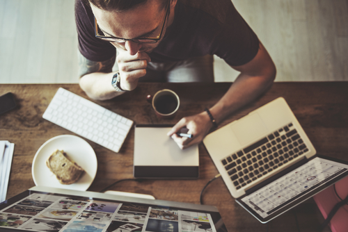 man sitting at table with laptop and coffee