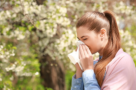 Young woman sneezing outside